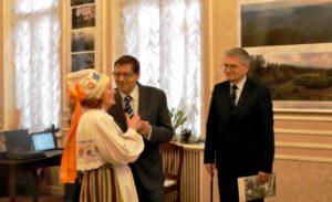"""Leonida Brashkinat folkloorirühma """"Neevo"""" endist juhendajat õnnitlevad möödunud 85. juubeli puhul endine konsul Jüri Trei ja Kultuuriministeeriumi nõunik Madis Järv"""